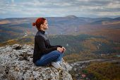 Young Fitness Woman Practice Yoga At Mountain Peak Cliff Edge poster