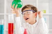 Astonished Little Scientist In Safety Goggles Looking At Green Liquid In Flask While Conducting Chem poster