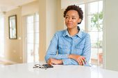 Young beautiful african american woman smiling looking side and staring away thinking. poster