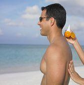Mulher espalhando protetor solar nas costas do namorado