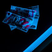 Selective Focus Of Blue Ultraviolet Lightning On Russian Money On Black poster