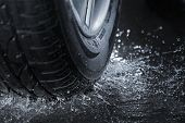 Car tire splashing in water.