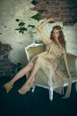 Portrait of a beautiful red-haired young woman sitting in vintage armchair. Hippie style. Bohemian s poster