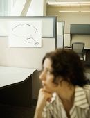 Businesswoman thinking near dry erase board with empty thought bubble on it