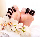 Mujer que recibe el masaje con piedras calientes en los pies. Aislado.