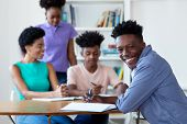 African American Male Student Learning At Desk At School With Teacher And Group Of Students At Class poster