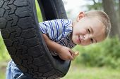 picture of tire swing  - Portrait of a young boy winking while swinging on tire - JPG