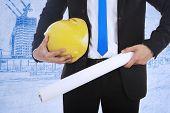 Businessman Holds Safety Helmet And Blueprint