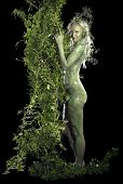 picture of faerie  - bodypainted woman in front of dark back partly hidden by green vegetation - JPG