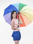 Picture of asian girl of indian origin with rainbow umbrella.