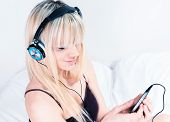 Cute Blond Girl Listening To Music On Her Smartphone