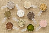 scoops of superfood - healthy seeds and powders (white and black chia, flax, hemp, pomegranate fruit
