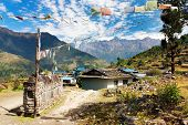 Prayer wall, prayer flags and village in Nepal