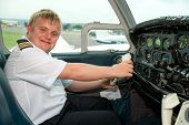 Portrait Of Young Pilot With Down Syndrome In Cabin.