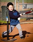 Boy batting at t-ball practice