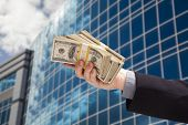 Male Hand Holding Stack of Cash with Corporate Building Background.
