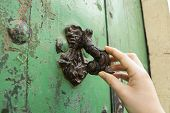 a woman's hand holding a door knocker