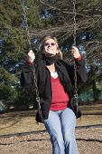 stock photo of swingset  - Adult woman looking up in setting winter sun as she swings on a swingset - JPG