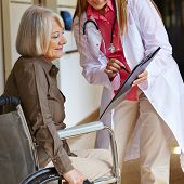 Nurse in a hospital asking a senior woman in wheelchair for signature