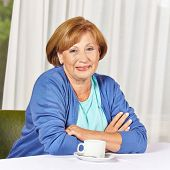 Smiling female senior citizen sitting at coffee table in retirement home