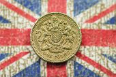 stock photo of golden coin  - One Pound Money Coin on British Flag - JPG