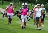 KUALA LUMPUR - OCTOBER 12: IK Kim (white) and Amy Yang (stripes) walk with their caddies to Hole 2 of the KLGCC course on Day 3 of the Sime Darby LPGA on October 12, 2013 in Kuala Lumpur, Malaysia.