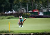 KUALA LUMPUR - OCTOBER 12: Michele Wie of USA lines up her putt on the 2nd hole green of the KLGCC course on Day 3 of the Sime Darby LPGA on October 12, 2013 in Kuala Lumpur, Malaysia.