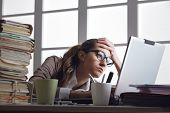 image of depressed  - Businesswoman frustated with work has a lot of paperwork at the office - JPG