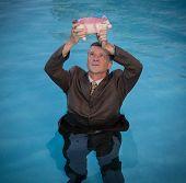 Senior Man Holding Piggy Bank Above Water