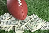 Football On Field With A Pile Of Money