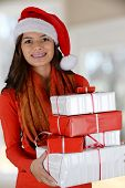 Happy teen girl smiling while holding christmas gifts