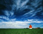 Orange Grain Elevator Against A Big Blue Sky.