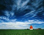 Orange Grain Elevator Against A Big Blue Sky.