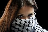 Girl with beautiful eyes wearing a palestinian scarf over her face on a dark background