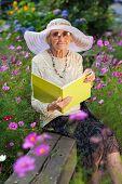 Elegant Elderly Lady Reading In The Garden