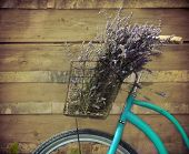 foto of wooden basket  - Vintage bicycle with basket with lavender flowers near the wooden wall