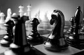 stock photo of foreground  - Close up low angle corner view of chess pieces lined up on a chess board ready for a game with focus to a black pawn with a castle and knight in the foreground - JPG