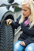 a young woman is measuring the tread depth of her car tire. the proper depth in the tread of a tire