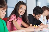 pic of classmates  - Portrait of happy teenage girl sitting with classmates studying at desk in classroom - JPG
