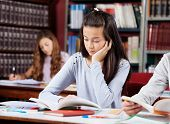 Teenage girl reading book at table with friends in school library