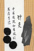 Acupuncture needles with rehmannia root and mandarin script on rice paper over bamboo. Sheng di huang. Translation describes acupuncture  medicine as a traditional and effective medical solution.