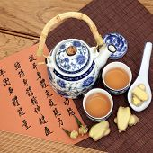 Ginger tea used in chinese herbal medicine with mandarin calligraphy on rice paper and teapot.  Tran