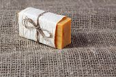 stock photo of personal hygiene  - piece of natural soap tied with twine on a linen cloth - JPG