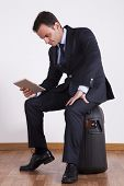 Businessman sit on a travel luggage using a digital tablet
