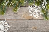 Christmas fir tree and decor covered with snow on wooden board background