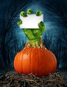 stock photo of monster symbol  - Zombie pumpkin sign with a green hand holding a blank sign card as a creepy halloween or scary symbol with textured skin wrinkled monster fingers coming out of a wet open pumpkin in a dark spooky forest - JPG