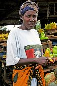 African Woman Cutting Fruit at Local Market
