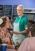 foto of patron  - Older cafe worker with patrons in restaurant