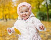cheerful little girl among autumn  leaves