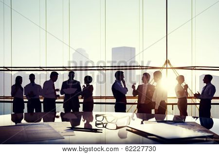 Group of Business People Discussing at Sunset Reflected Onto Table with Documents. poster